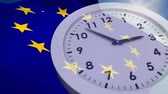 miara : Digital composite of European and UK flag waives behind a white analog clock. Background of the sky with sun.