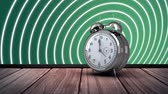 watch icon : Digitally generated alarm clock on a wooden deck with green wall. Circular patterns spreading. Stock Footage