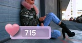 profil : Side view of a punk woman sitting on a sidewalk typing on her phone smiling. In the foreground is a digital animation of a pink heart icon with increasing numbers. 4k