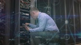 technician : Side-view of a technician inspecting a data server rack using a computer tablet  with blockchain technology animation. Stock Footage