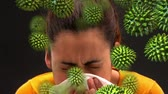 educação : Digital composite of a close-up view of a middle-aged mixed-race woman sneezing with with green pollen grains moving towards her face Stock Footage