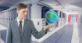 server : Digital animation of a young Caucasian male technician in business suit raising his hand and showing an Earth hologram with rotating , in an aisle view of a server room 4k Stock Footage