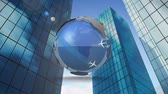 графический : Digital animation of a rotating 3d world with moving airplanes around it, on a low-angle view of a series of skyscrapers