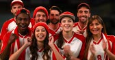 дриблинг : Front view of sports fans, wearing white and red jerseys, cheering as a group. 4k