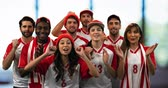 drible : Front view of a group of sports fans wearing red and white jerseys cheering loudly 4k