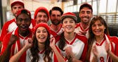 taps : Front view of a group of sports fans wearing red and white jerseys lively cheering 4k