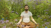 denge : Front view of a Caucasian man Meditating in a garden filled with flowers