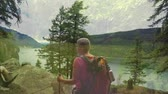 hiking trail : Digital composite of an old Caucasian woman hiking in the woods. She is gazing at a high angle view of a lake and mountains Stock Footage