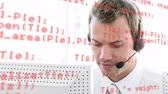 diyalog : Digital composite of a male Caucasian call centre agent talking while typing and computer codes in the foreground Stok Video