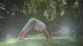 out of focus : Side view of woman doing yoga at a park. Bokeh lights can be seen falling in forground
