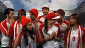 derrota : Front view of male and female fans wearing red and white jerseys feeling sad at a game in stadium Stock Footage