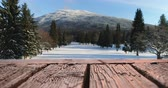 algida : Digital composite of a wooden deck with a background of a snowy field with the view of a mountain and pine trees 4k Filmati Stock