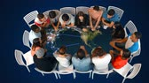 setkání : Digital composite of diverse people seated while table shows a world map with glowing lines