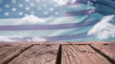 usa : Digital composite of a wooden deck with a view of an American flag waving Dostupné videozáznamy