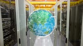 disk : Digital animation of a globe with glowing white lines rotating in a hallway of server towers Stok Video