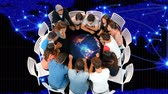 explicando : Digital composite of diverse group of people seated in a table with a display of a globe with glowing lines and background of a world map with glowing lines