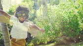 stodola : Digital composite of an African-American girl playing in the garden while wearing goggles and carton wings