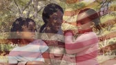 stodola : Digital composite of an African-American mother in military uniform with daughters in the park while background shows an American flag waving