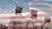 saluto militare : Digital composite of military men in uniform saluting at a park while an American flag waves in the background Filmati Stock