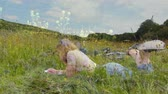 stodola : Digital composite of a Caucasian woman lying on the grass while writing with background of field of flowers Dostupné videozáznamy