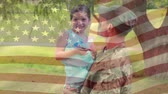 família : Digital composite of an American soldier carrying his daughter while she is holding a mini flag with an American flag waving in the foreground