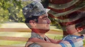 família : Digital composite of a soldier talking to his son while carrying him in his arms with an American flag waving in the foreground