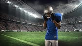 antreman : Digital animation of an African-american football player putting on his helmet with a digital field stadium background Stok Video
