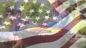 billowing : Digital composite of a family having a picnic barbecue with an American flag waving in the foreground