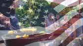 drapeau usa : Digital composite of a man cooking for his friends at a picnic barbecue with an American flag waving in the foreground. Behind him you can see his friends sitting on a picnic table sharing stories
