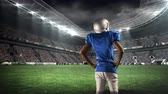 viraj : Rear view of an African-american football player standing on a digitally generated field stadium Stok Video