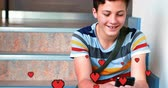 enamoramiento : Digital composite of a Caucasian boy sitting in the stairs smiling while texting and digital hearts flying in the foreground 4k Archivo de Video