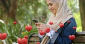 enamoramiento : Digital composite of a Muslim woman wearing a hijab, sitting on a park bench smiling while texting and digital hearts flying in the foreground 4k