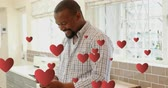 enamoramiento : Digital animation of an African-american man texting and smiling in kitchen. Floating hearts are seen in the foreground 4k