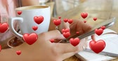 devoção : Close up of a pair of female hands texting beside a cup of coffee and a pen and notebook. Digital hearts are flying in the foreground 4k