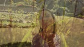 eğlendirmek : Digital composite of a Caucasian woman blowing a kiss outdoors with grass plants in the foreground Stok Video