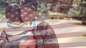 quality time : Digital composite of an American female soldier giving his son a big hug in the park with an American flag waving in the foreground