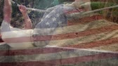 obstacle course : Digital composite of American soldiers crossing a rope with an American flag waving in the foreground Stock Footage