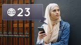 цифровая технология : Digital composite of woman in hijab leaning on a wall near a gate while texting. Beside her is a notifications icon with increasing count for social media Стоковые видеозаписи