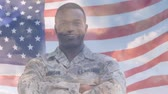 saluto militare : Digital animation of American flag waving behind African-American military man in uniform smiling while background shows the sky with clouds.