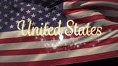 patriota : Digital animation of gold United States text with bokeh lights while American flag waves in the background. Stock Footage