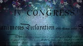 написанный : Digital animation of the written declaration of independence of the United States moving in the screen while dark background shows lights moving and colorful confetti slowly falling in the screen. Стоковые видеозаписи