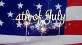 написанный : Digital animation of gold 4th of July text appearing while an American flag and cupcakes with lighted sparkles on top of a red and white striped table cloth pans in the screen