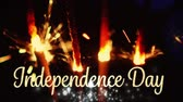 honra : Animation of the words independence day in a decorative golden font appearing over dark background with lit sparklers close up