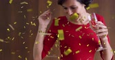flauta : Digital composite of a Caucasian woman holding a glass of champagne dancing while gold confetti fall in the screen.