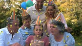 clubbing : Digital composite of a Caucasian girl about to blow the candles on her birthday cake. Beside her are her grandparents and behind her are her parents with her brother. The foreground has digital confetti