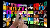 inscrição : Digital animation of a screen field with music videos. On the foreground is  a pair of hands holding a smartphone with music on the screens