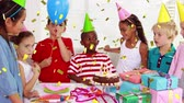 narodziny : Digital composite of an African-American boy blowing candles on a birthday cake while surrounded by diverse kids celebrating his birthday party and gold confetti falling in the screen