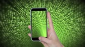 fonte : Digital composite of a hand holding a mobile phone while screen and background shows a green matrix of binary codes zooming in the screen Stock Footage