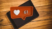 suscribete : Digital composite of a tablet on top of a wooden table and an orange message bubble with a heart icon and increasing numbers for social media Archivo de Video