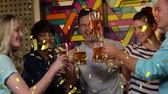 relação : Digital composite of a group of diverse friends celebrating over drinks while gold confetti fall in the screen Stock Footage